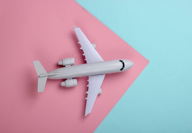Spielzeugmodell eines passagierflugzeugs auf einem blau-rosa pastell. das konzept von tourismus, flugreisen, minimalismus.