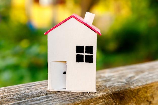 Spielzeugmodellhaus in holzszene in der nähe von grünem hintergrund. öko-dorf-immobilienhypothek-konzept