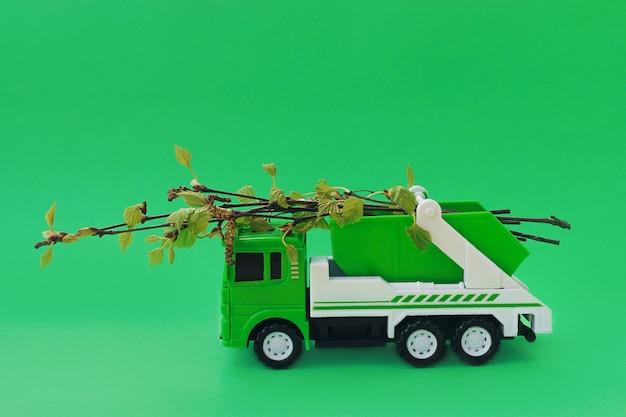 Spielzeugmüllwagen trägt frische zweige von bäumen