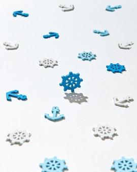 Spielzeugmuster von schiffssymbolen schiffsanker und ruder auf einem licht mit harten schatten. flach liegen.