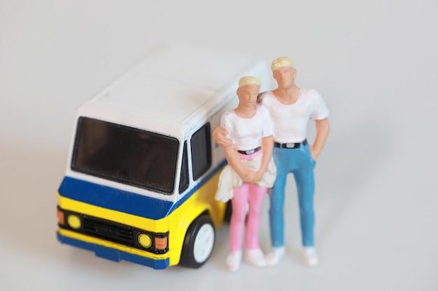 Spielzeugpaar mann und frau stehen in der nähe von mini-van-auto für reisen auf weißen, isolierten figurentouristen