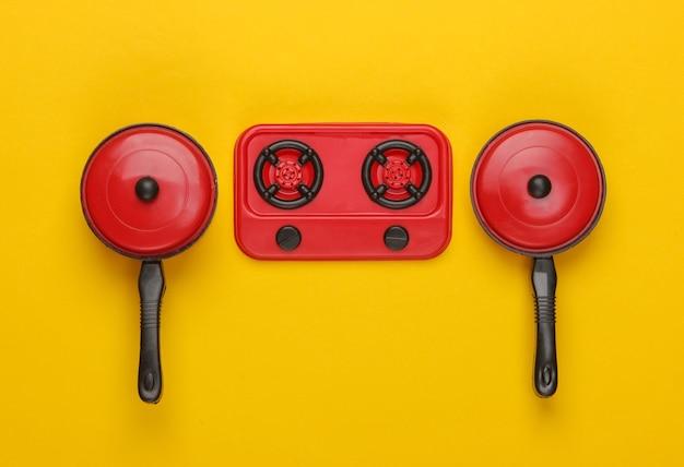 Spielzeugplastikofen mit pfannen auf gelb. kinderküche., minimalismus