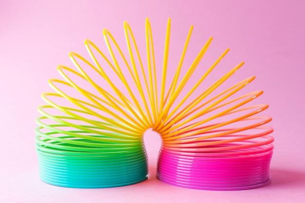 Spielzeugplastikregenbogen auf einem pastellrosa