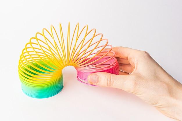 Spielzeugplastikregenbogen in den händen auf einem hellen hintergrund.