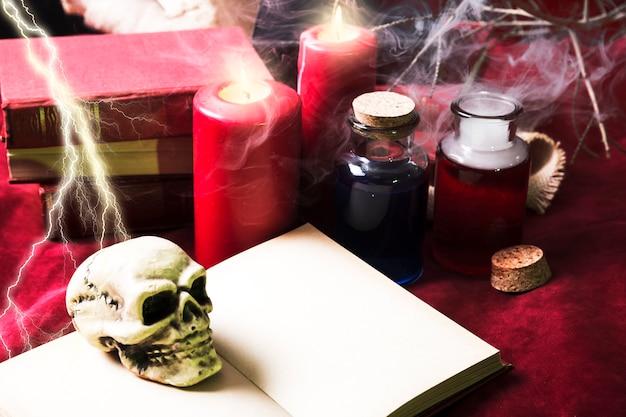 Spielzeugschädel auf buch mit halloween-dekorationen
