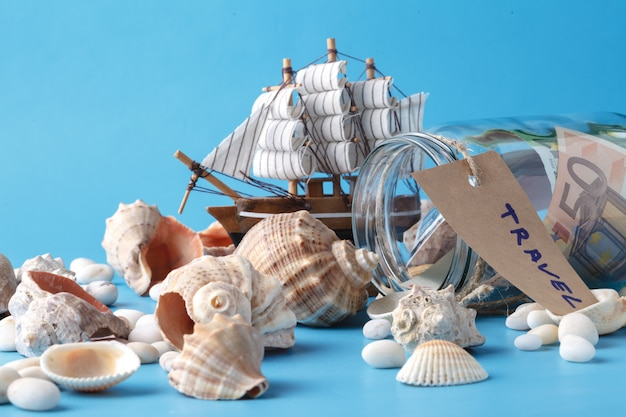 Spielzeugschiff, geldglas und muscheln
