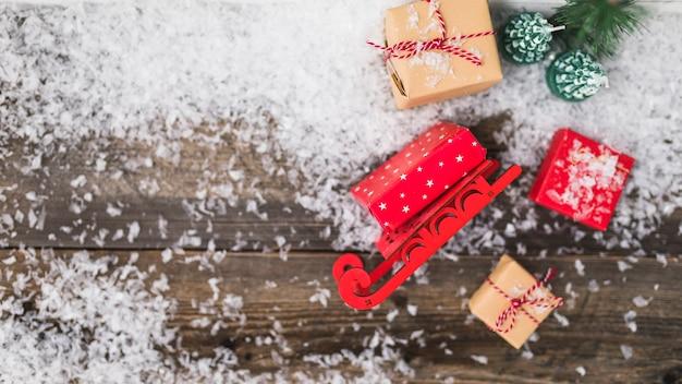 Spielzeugschlitten nahe präsentkartons zwischen schneeflocken