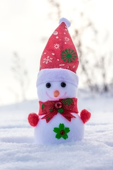 Spielzeugschneemann draußen im schnee. kalter wintertag_