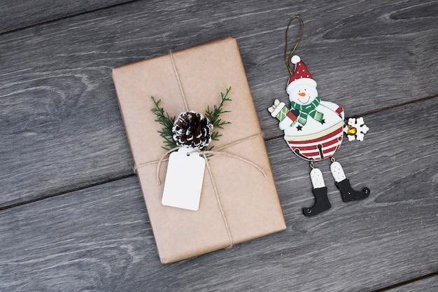 Spielzeugschneemann nahe geschenk in der verpackung mit baumstumpf und tag