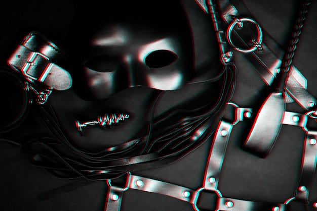 Spielzeugset für bdsm sex. lederflogger, handschellen, gürtel, halsband, maske und metall-analplug. schwarz und weiß mit glitch-effekt