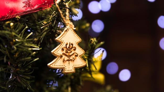 Spielzeugtannenbaum, der am weihnachtsbaum hängt