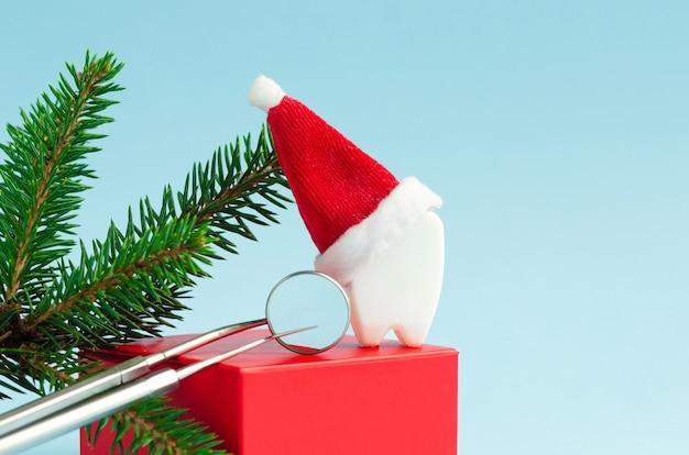Spielzeugzahn in weihnachtsmütze mit spiegel und sonde für neues jahr. kreative zahnärztliche weihnachten