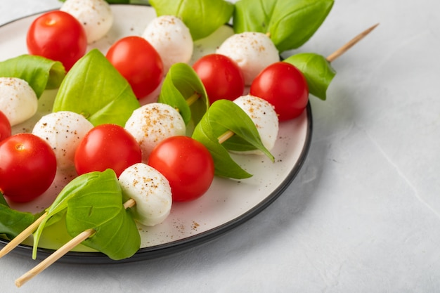 Spieß mit tomate, mozzarella und basilikum.