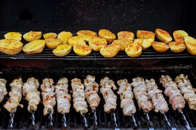 Spieße aus kartoffeln und fleisch sowie kebabs auf dem grill im freien