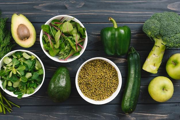 Spinat; avocado; paprika; brokkoli; apfel; gurke auf schreibtisch aus holz