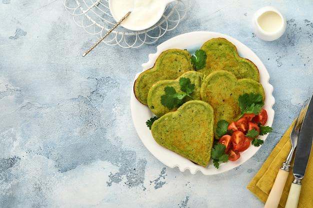 Spinat-avocado-pfannkuchen in herzform mit griechischer joghurtsauce und kirschtomaten auf weißem teller über hellgrauem hintergrund. frühstückskonzept. draufsicht mit kopienraum.