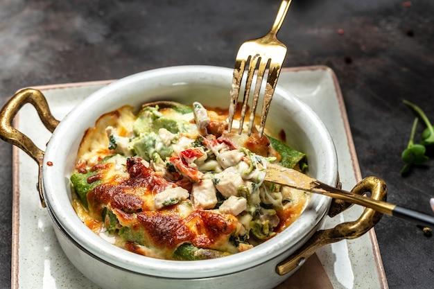Spinat-crpes oder pfannkuchen mit hühnchen und champignons mit käse überbacken. ein warmes kontinentales frühstück. hintergrund für lebensmittelrezepte. nahansicht.