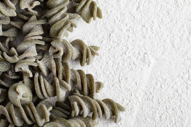 Spinat fusilli trockene nudeln auf betontisch. glutenfreie pasta.