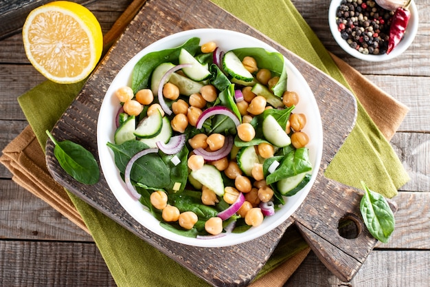 Spinat, gurke, kichererbsen, zwiebeln und zitronensalat auf einem holztisch