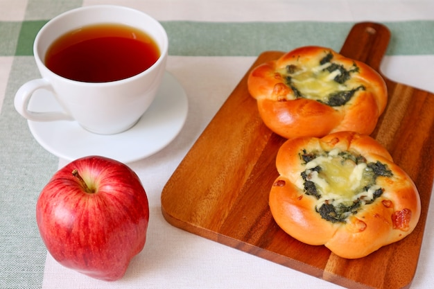 Spinat-käse-brötchen mit einer tasse heißem tee und apfel für eine schnelle mahlzeit