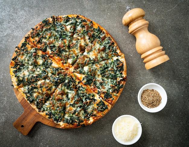 Spinat-käse-pizza auf holztablett - vegane und vegetarische küche