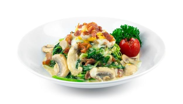 Spinat mit sahnesauce, bacom champignon pilzen und käse italienischer fusionsstil hausgemachte tellerdekoration petersilie und tomate seitenansicht