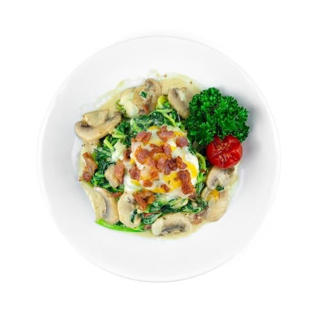 Spinat mit sahnesauce, bacom champignon und käse italienischer fusionsstil hausgemachte tellerdekoration petersilie und tomate draufsicht