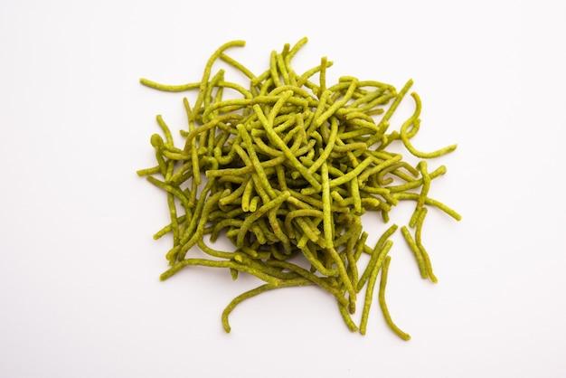 Spinat oder palak sev sind knusprig gebratene herzhafte nudeln. hausgemacht dickes und dünnes grünes shev oder namkeen ist ein klassischer indischer snack. in einer schüssel oder einem teller serviert