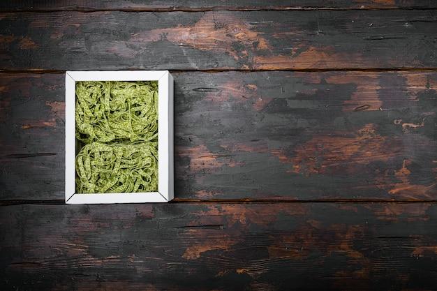 Spinat-pasta-pack-set, auf altem dunklem holztischhintergrund, draufsicht flach, mit kopienraum für text