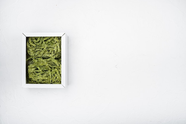 Spinat-pasta-pack-set, auf weißem steintischhintergrund, draufsicht flach, mit kopienraum für text