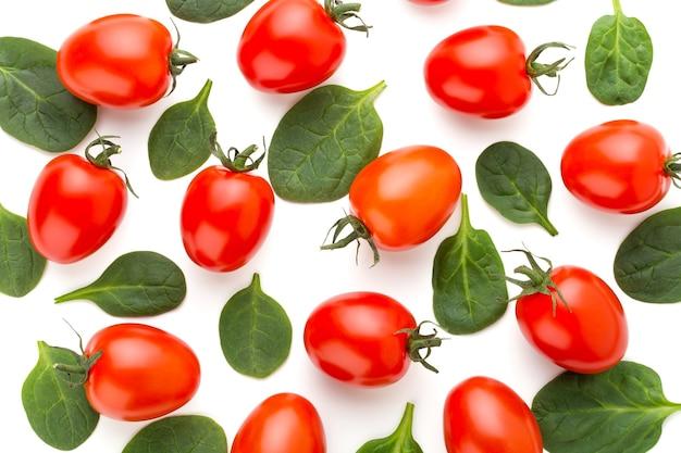 Spinat und tomatenmusterhintergrund auf weiß. draufsicht