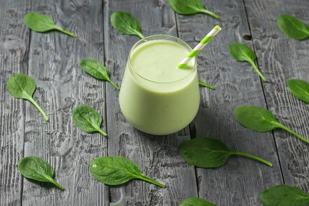Spinatblätter auf einem holztisch und einem glasglas mit einem smoothie. fitnessprodukt. diätetische sporternährung.