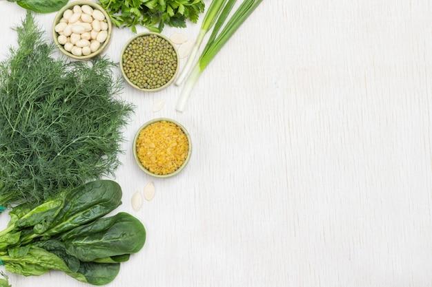 Spinatblätter, dill, frühlingszwiebeln und mungbohnen, nüsse und bulgur auf dem tisch. weißer hintergrund. platz kopieren