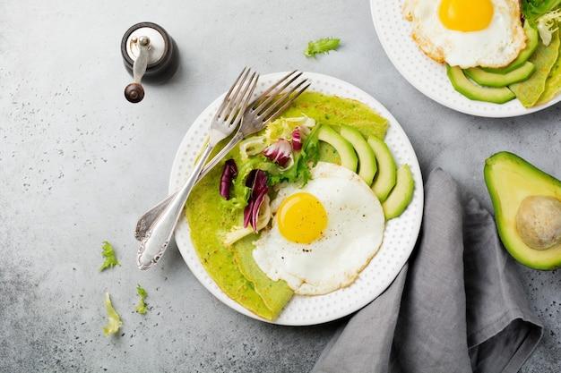 Spinatgrüne crepes (pfannkuchen) mit spiegelei, avocado und salatmischungen auf keramikplatte auf grauer betonoberfläche. selektiver fokus. draufsicht. copt raum.
