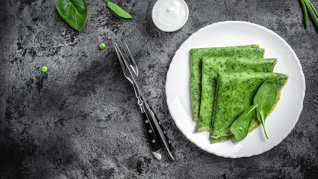 Spinatgrüne pfannkuchen crepes auf dunklem hintergrund. köstliches gesundes frühstück in der weißen platte. banner, menürezeptplatz für text, draufsicht.