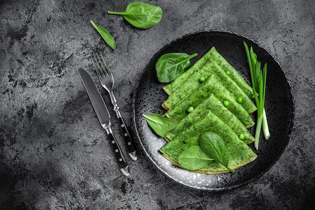 Spinatgrüne pfannkuchen crepes mit spinat und gemüse. vegetarisches essen, banner, menürezeptplatz für text, draufsicht.