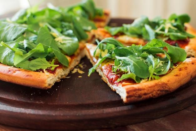 Spinatspitzen auf der scheibe der pizza über hölzernem behälter