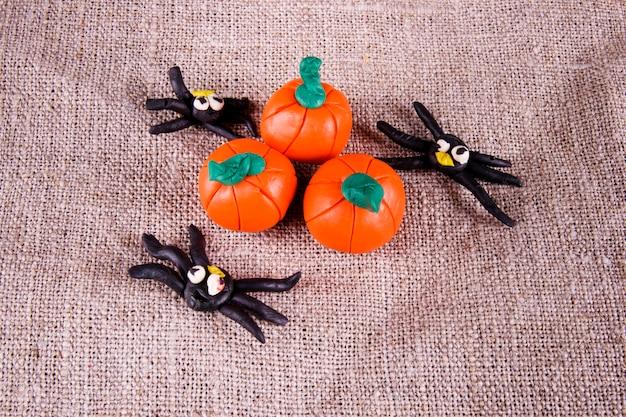 Spinnen und kürbisse halloween-konzept auf zerknittertem grauem hintergrund