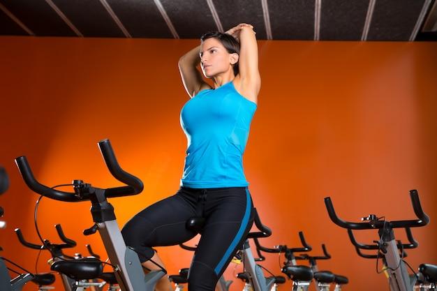 Spinnende frau der aerobic, die übungen nach training ausdehnt