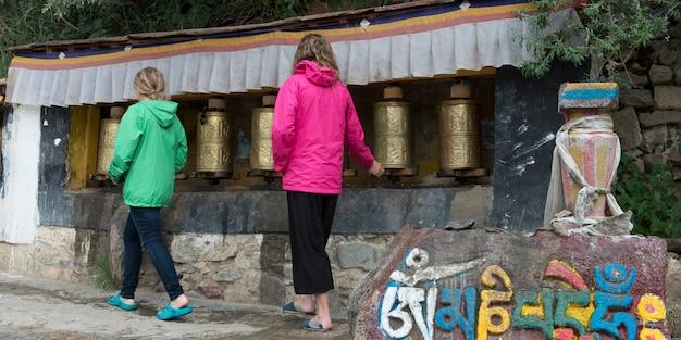 Spinnende gebetsräder der mädchen an drepung-kloster, lhasa, tibet, china