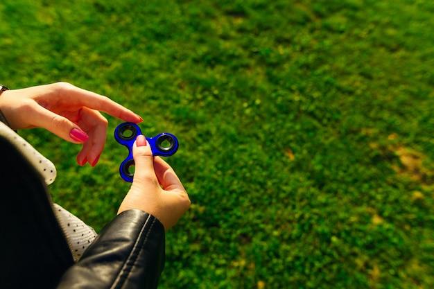 Spinnender spielzeugspinner in den händen eines mädchens auf grünem hintergrund.