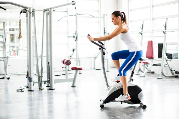 Spinnendes frauenübungstraining der aerobics an der fahrradgymnastik
