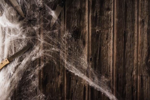 Spinnennetz auf holzhintergrund mit messern. halloween-banner. platz kopieren. selektiver fokus.
