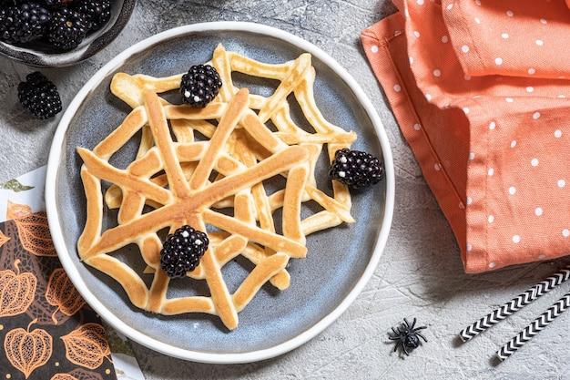 Spinnennetzpfannkuchen mit brombeere zum halloween-frühstück