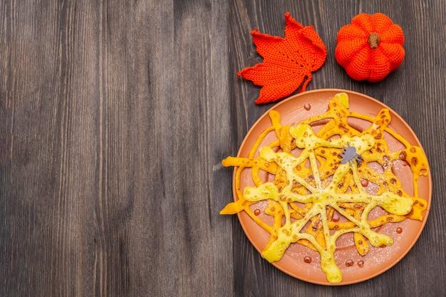 Spinnennetzpfannkuchen mit zuckersirup und -pulver zum halloween-frühstück. mit gehäkeltem orangenkürbis und blatt