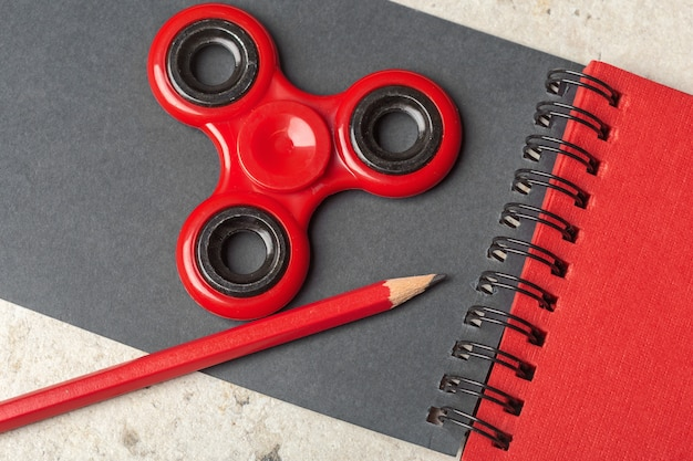 Spinner, notizbuch und bleistift auf dem tisch