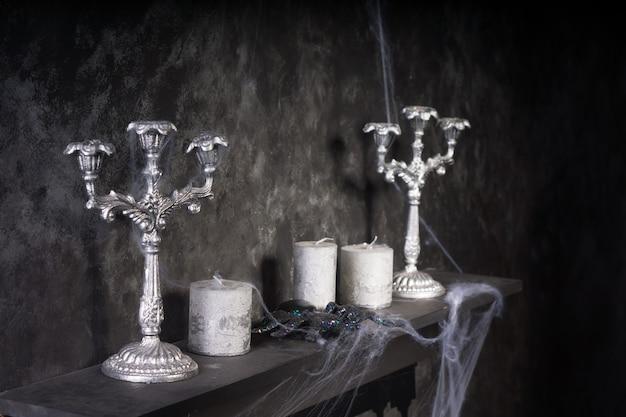 Spinnwebenbedeckte kerzen und kandelaber auf dem mantel in einer unheimlichen geisterhaus-umgebung
