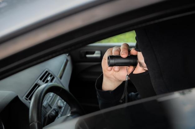 Spionage aus dem auto. mann mit fernglas in schwarzer kleidung. kriminelles konzept. detektivarbeit.