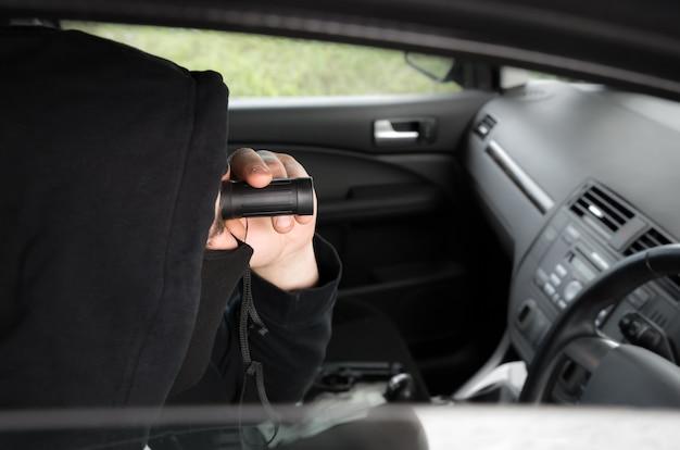 Spionage aus dem auto. mann mit fernglas in schwarzer kleidung. kriminelles konzept.