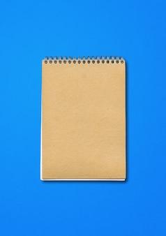 Spiral geschlossenes notizbuchmodell, braune papierabdeckung, lokalisiert auf blauem hintergrund